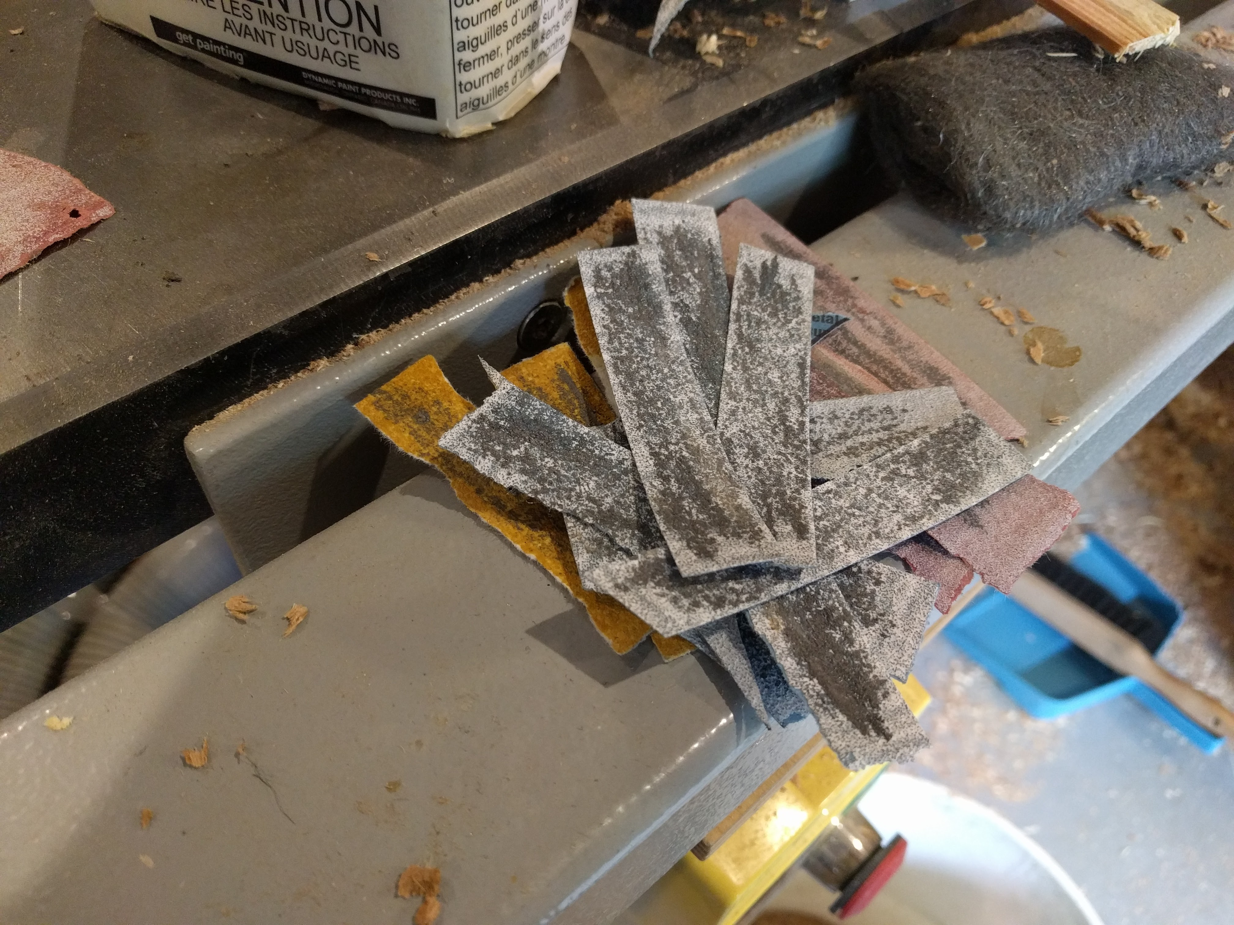 Sandpaper strips used to shape the stainless steel part.